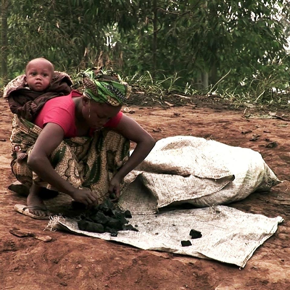 mujer limpiando coltan con niño a cuesta - foto
